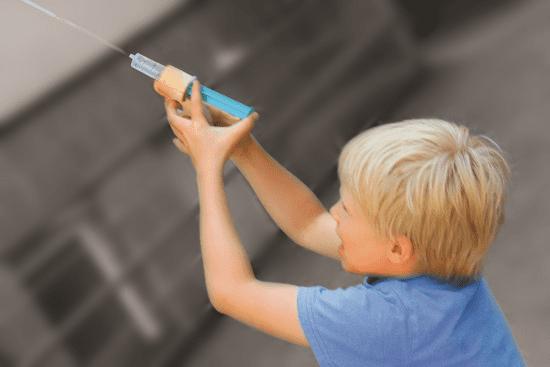 kind speelt met houten waterpistool en spuitje